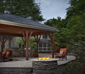 Located in Charlotte, NC this backyard oasis was designed and constructed by Archadeck. It includes a pool deck, screened porch, covered outdoor kitchen and dining area, firepit and raised spa deck.